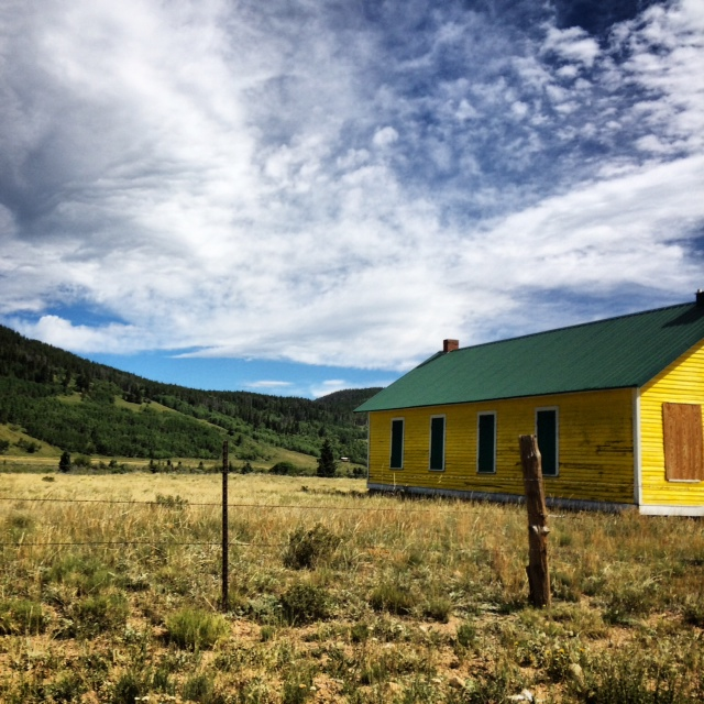 Isolation. This house, vibrant yellow, sits alone in a massive valley.